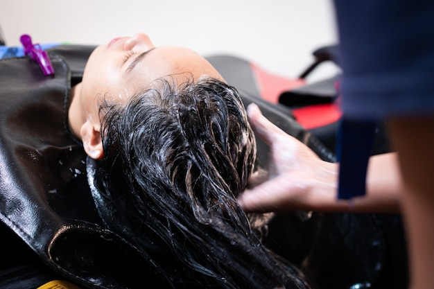 Young asian woman getting a hair wash by hairdresser at hair salon. hairdresser washing hair of a young woman with shampoo and massage her head.
