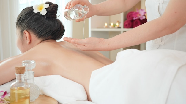 Young asian woman getting relaxing oil massage at beauty spa salon. massage for health, pour essential oil