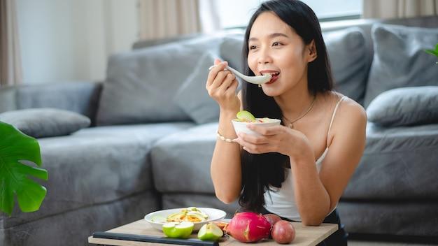 Молодая азиатская женщина-девочка, держащая здоровую пищу из свежих овощей в образе жизни дома, красивая женщина-вегетарианка, делающая диетическое питание, ест салат, люди улыбаются счастливыми, концепция здорового питания