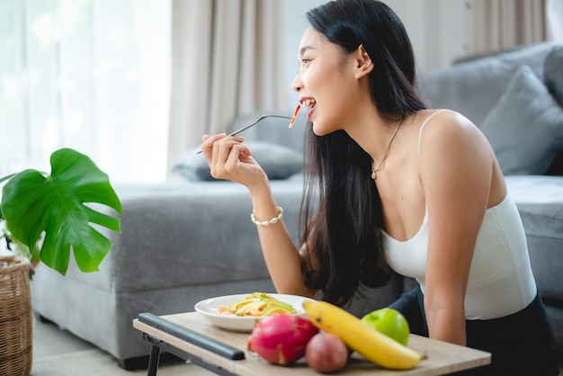 Молодая азиатская женщина-девочка, держащая здоровую пищу из свежих овощей в образе жизни дома, красивая женщина-вегетарианец, делающая диетическое питание, ест салат, люди улыбаются счастливыми, концепция здорового питания