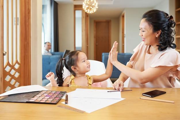 Молодая азиатская женщина дает пять своей маленькой дочери после того, как они закончили рисовать