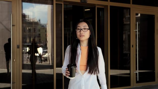 Молодая азиатская женщина выходит из современного здания и пьет кофе на открытом воздухе портрет