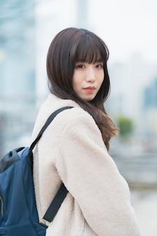 Молодая азиатская женщина выходит с рюкзаком на спине