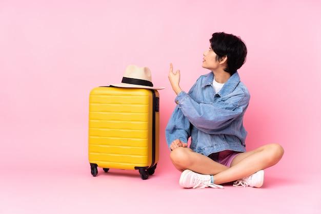 孤立した背景の上を旅行する若いアジア女性
