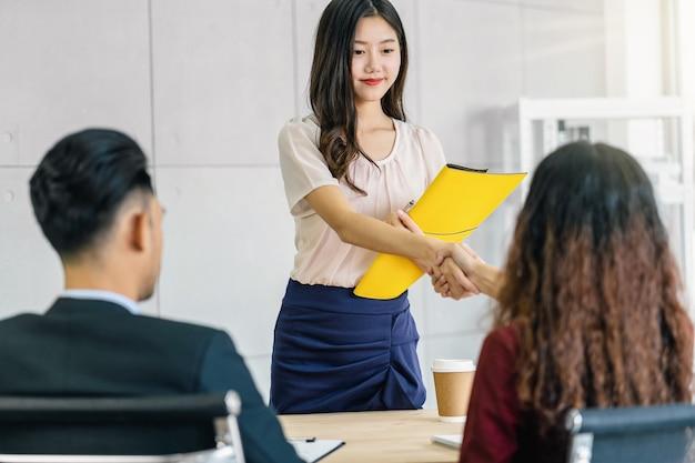 Молодая азиатская женщина-выпускница пожимает руку двум менеджерам, чтобы приветствовать их перед началом собеседования
