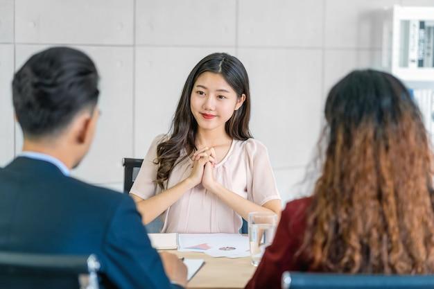 긍정적인 움직임으로 두 명의 관리자와 인터뷰하는 젊은 아시아 여성 졸업생