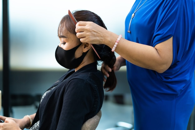 Young asian woman at hairdresser salon wearing surgical protective face mask. new normal and social distancing concept