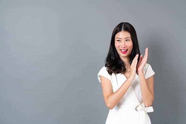 若いアジアの女性は灰色の壁に幸せで興奮した顔で手をたたく