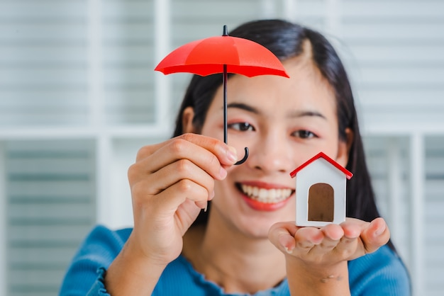Young asian woman hand hold umbrella toy to protect the home.