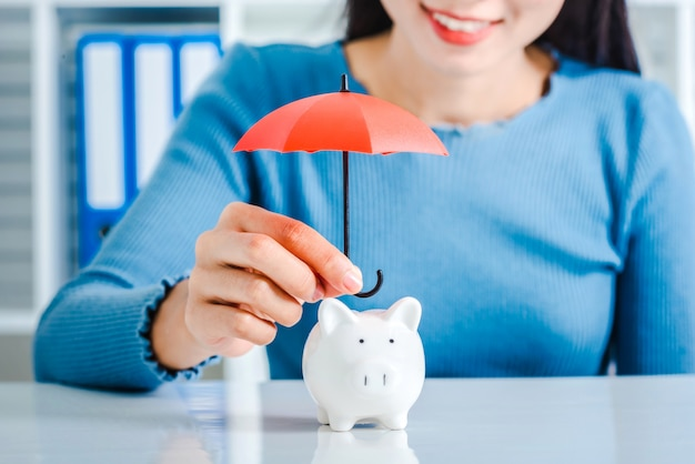 Young asian woman hand hold umbrella toy to protect piggy bank.