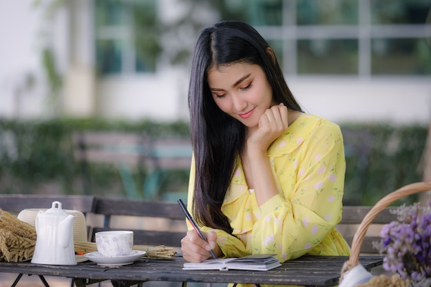 Young asian woman hand is writing on notepad with a pen in the garden