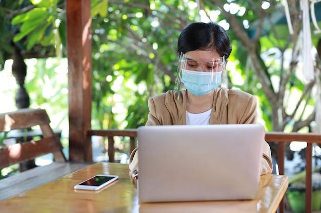 若いアジア人女性は、ヘルスケア用の保護マスク付きのカジュアルなドレスを着て、喫茶店に座ってスマートフォンで使用し、ラップトップコンピューターで作業しています。新しい通常および社会的距離の概念