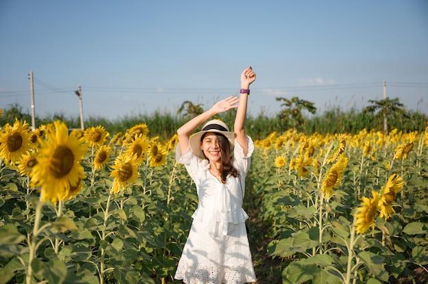 젊은 아시아 여성의 행복과 저녁에 시골에서 해바라기 밭에 팔을 올리는