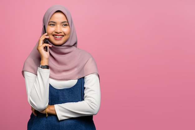 幸せで携帯電話で話している若いアジアの女性