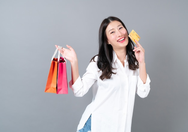 Young asian woman happy smiling holding credit card and shopping bags in white shirt on grey background