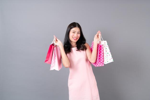 ショッピングバッグを持って幸せな笑顔の若いアジアの女性