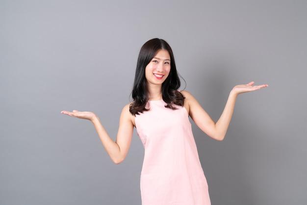 灰色の壁にピンクのドレスで幸せな笑顔の若いアジアの女性