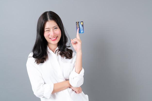 회색에 손에 젊은 아시아 여자 행복 미소 현재 신용 카드