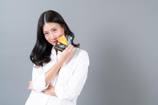 若いアジアの女性幸せな笑顔プレゼントクレジットカードを手に灰色