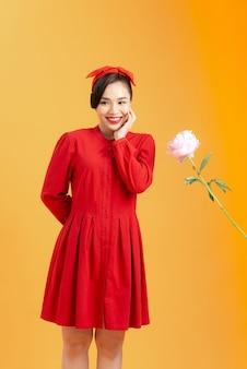 젊은 아시아 여성은 주황색 배경에 고립되어 서 있을 때 모란 장미를 받는 것을 기쁘게 생각합니다.