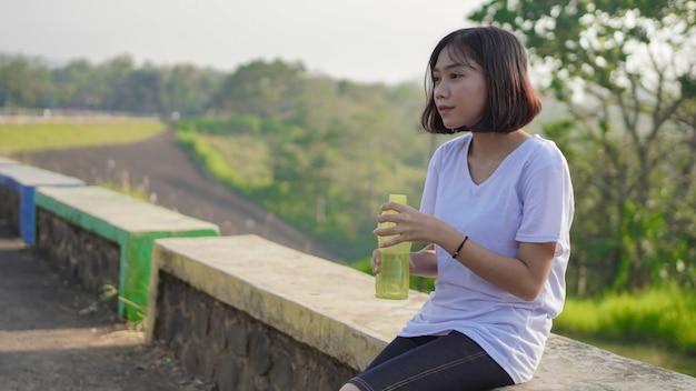젊은 아시아 여성은 아침에 조깅을 한 후 술을 마시고 휴식을 취합니다
