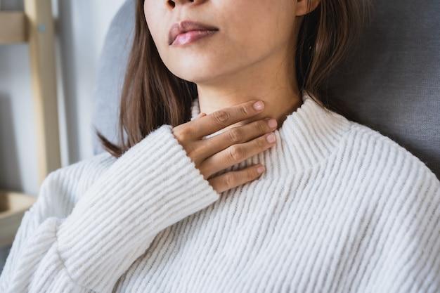 Молодая азиатская женщина имея кашель, боль в горле и страдая от холода зимой