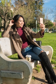 Young asian woman having a video call sitting in a bench in the park.