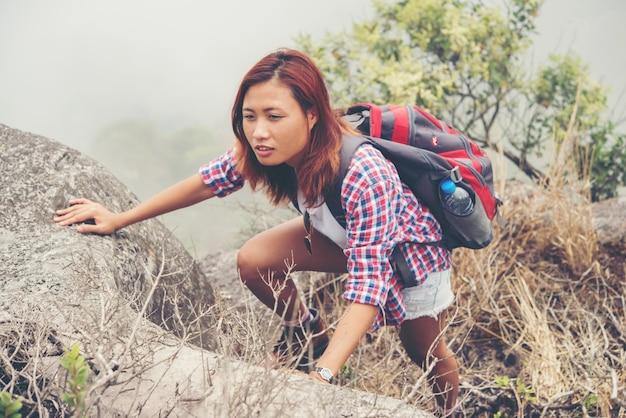 Young asian woman hiker climbing rock on mountain peak cliff.
