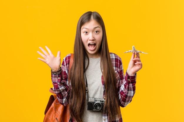 勝利または成功を祝う飛行機のアイコンを保持している若いアジアの女性