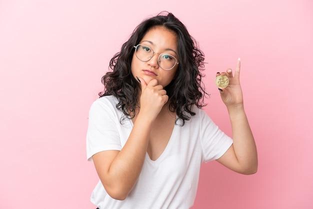 疑いと思考を持っているピンクの背景に分離されたビットコインを保持している若いアジアの女性