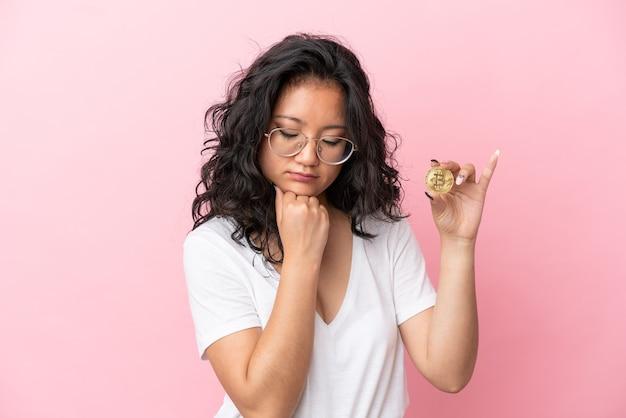 疑いを持っているピンクの背景に分離されたビットコインを保持している若いアジアの女性