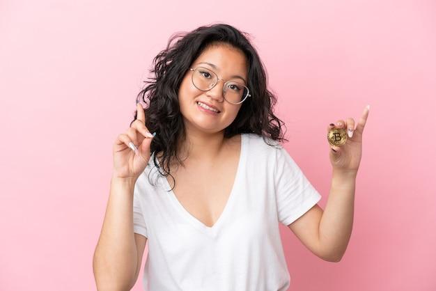 Молодая азиатская женщина, держащая биткойн на розовом фоне, показывает и поднимает палец в знак лучших