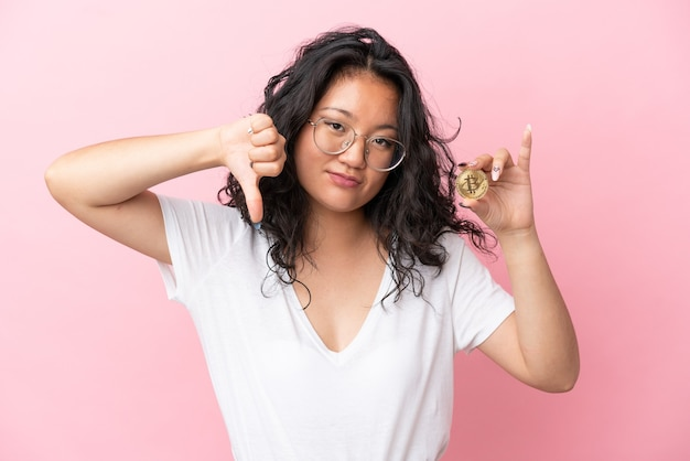 부정적인 표정으로 엄지손가락을 아래로 보여주는 분홍색 배경에 고립 된 bitcoin을 들고 젊은 아시아 여자