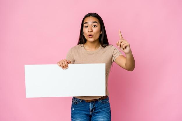 Молодая азиатская женщина, держащая чистый лист бумаги для белого что-то на изолированном фоне, имея идею, концепцию вдохновения.