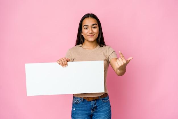Молодая азиатская женщина держит чистый лист бумаги для чего-то белого над изолированной стеной, указывая пальцем на вас, как будто приглашая подойти ближе.