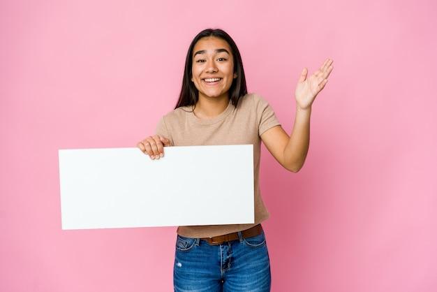 즐거운 놀라움을 받고 고립 된 벽 위에 흰색 뭔가 빈 종이를 들고 젊은 아시아 여자, 흥분하고 손을 올리는