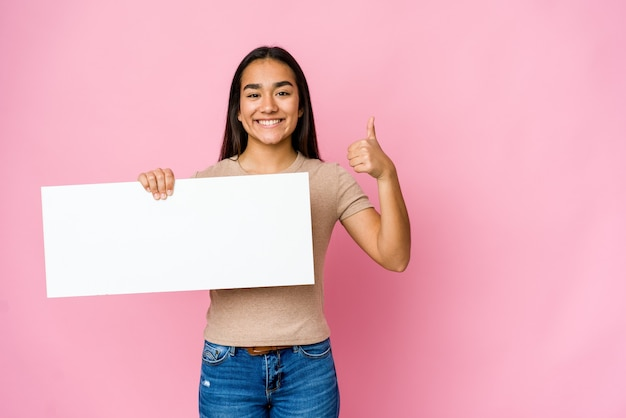 Молодая азиатская женщина держит чистый лист бумаги для чего-то белого над изолированной стеной, улыбаясь и поднимая большой палец вверх