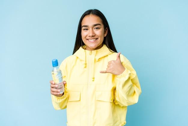 指で携帯電話の呼び出しジェスチャーを示す青で隔離の水のボトルを保持している若いアジアの女性。