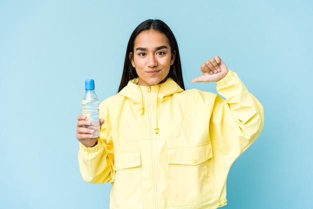 파란색 벽에 절연 물 한 병을 들고 젊은 아시아 여자는 예를 따라 자랑스럽고 자신감을 느낍니다.