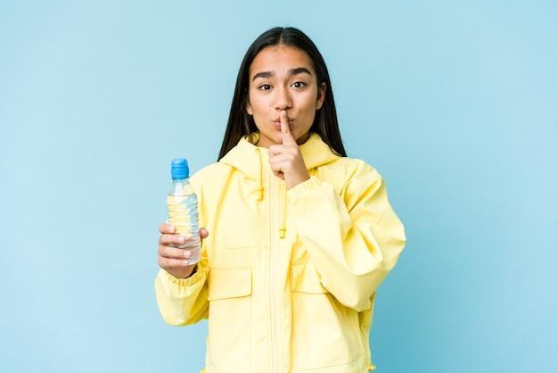 비밀을 유지하거나 침묵을 요구하는 파란색 벽에 절연 물 한 병을 들고 젊은 아시아 여자.