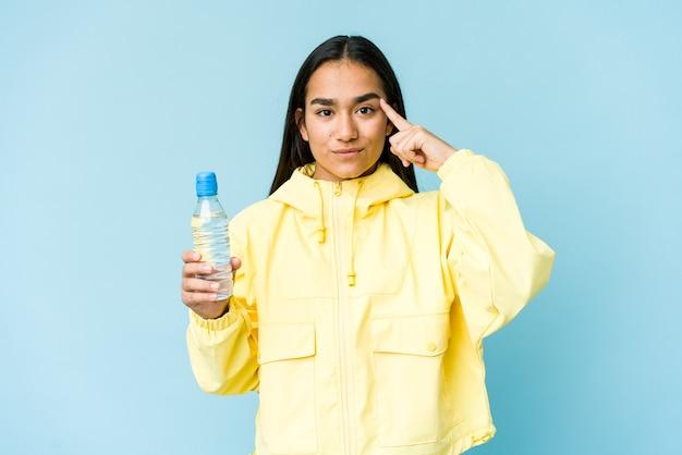 青い壁に隔離された水のボトルを指で指して、考えて、タスクに焦点を当てた若いアジアの女性。