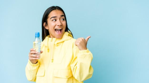 Молодая азиатская женщина, держащая бутылку воды, изолированную на синей стене, указывает пальцем далеко, смеясь и беззаботно.
