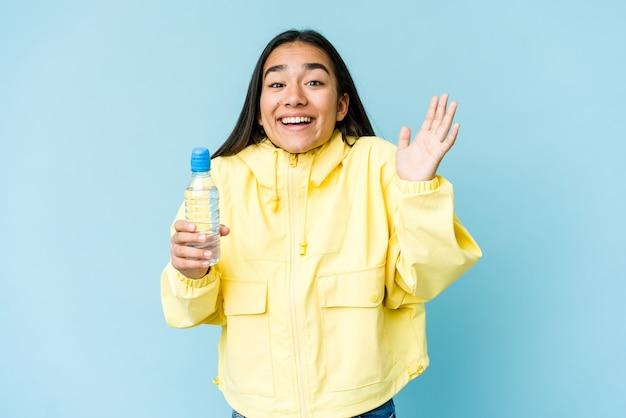 즐거운 놀라움을 받고, 흥분하고 손을 올리는 파란색 벽에 절연 물 한 병을 들고 젊은 아시아 여자.