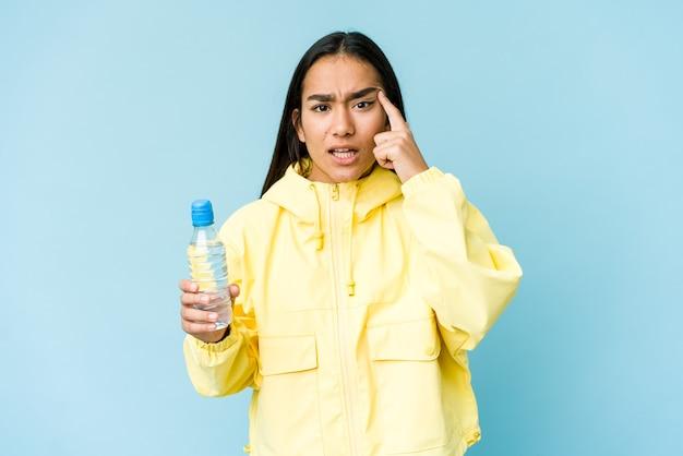 집게 손가락으로 실망 제스처를 보여주는 파란색 벽에 절연 물 한 병을 들고 젊은 아시아 여자.