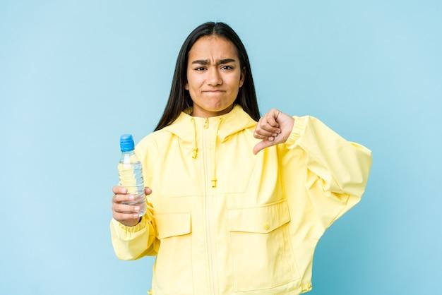 Молодая азиатская женщина держит бутылку воды, изолированную на синей стене, показывая жест неприязни, пальцы вниз. концепция несогласия.