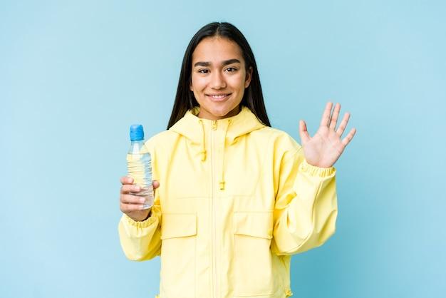 파란색 벽에 절연 물 한 병을 들고 젊은 아시아 여자 손가락으로 명랑 게재 번호 5 웃 고.