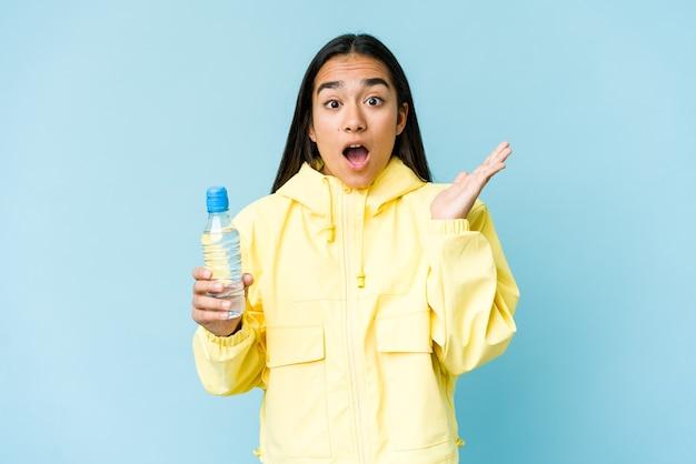 Молодая азиатская женщина, держащая бутылку воды, изолированную на голубой стене, удивила и потрясла.