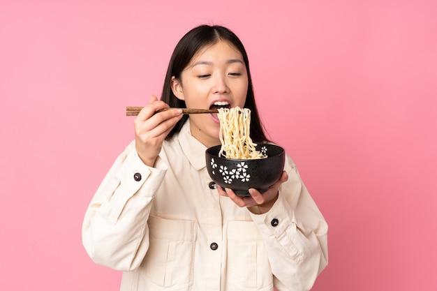 Молодая азиатская женщина держит миску лапши с палочками для еды и ест ее