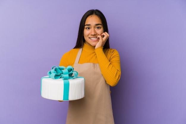 ケーキを持っている若いアジアの女性は、神経質で非常に心配して、爪を噛んで孤立しました。