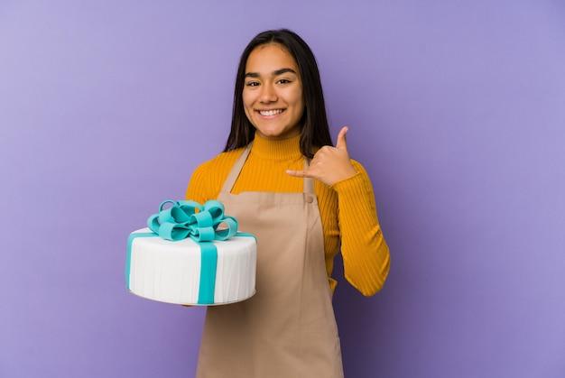 指で携帯電話の呼び出しジェスチャーを示す孤立したケーキを保持している若いアジアの女性。